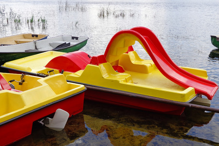 Boats and paddle boats in the shoal water Stock Photo