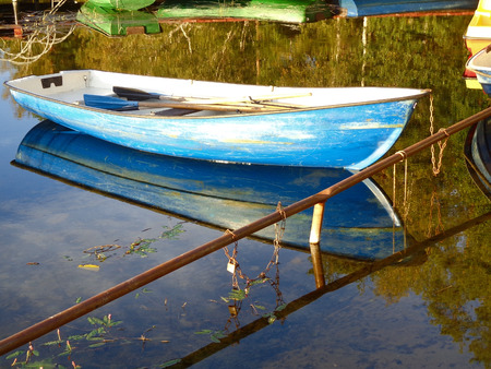 The anchored boat at the shore of the lake