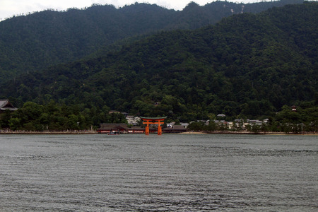 Gate temple by the beach. Far-away look of Itsukushima Shrine in Miyajima Island, Japan. The gate is standing in the middle of the sea. Pic was taken in August 2017 Editorial