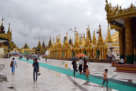 The national religious symbol of Burmese. Its the shwedagon Pagoda with its golden stupa, and many people visiting this place. Pic was taken in Yangon, Burma - August 2015.