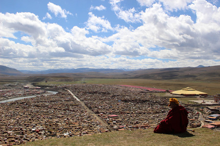 A Tibetan monk overlooking the Yarchen Gar (Yaqen Orgyan Temple) in Baiyu (or 'Pelyul') county, Garze, China - in March 2015. Banque d'images - 104859947