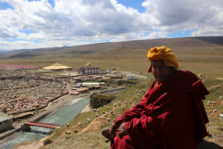A Tibetan monk overlooking the Yarchen Gar (Yaqen Orgyan Temple) in Baiyu (or 'Pelyul') county, Garze, China - in March 2015. Banque d'images - 104859948