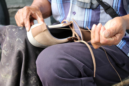 Process of manual shoe reparation, sole and welt fixing and stitching. Taken in Indonesia. Standard-Bild - 118641863