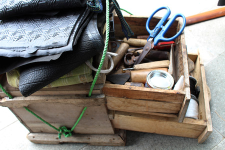 The equipment used for manual shoe sole sticthing stored in a wooden cart. Standard-Bild - 118641888