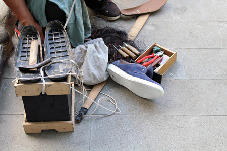 The equipment and tools used for manual shoe sole sticthing stored in a wooden cart.