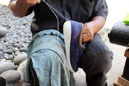 Process of manual shoe reparation, sole and welt fixing and stitching. Taken in Indonesia. Standard-Bild - 119658275