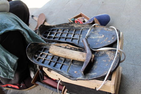 The equipment and tools used for manual shoe sole sticthing stored in a wooden cart. Standard-Bild - 119658432