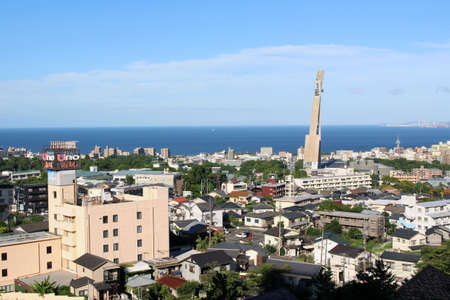 The panoramic view of Beppu City, its Tower, and the sea in Oita Prefecture, Japan. Taken in April 2019. Stock Photo