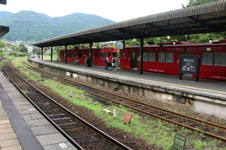 Red train stopping at Yufuin Station in Oita, Japan. Taken in June 2019