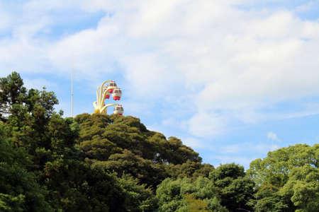 The attraction of ferris wheel of Rakuten-ji behind trees in Beppu, Oita, Japan. Taken in June 2019.