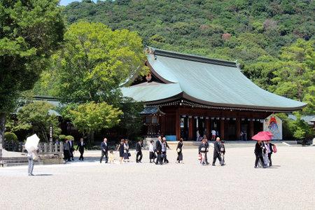 Japanese family taking photos in front of Kashihara Jingu Temple in Nara, Japan. Taken in September 2019.