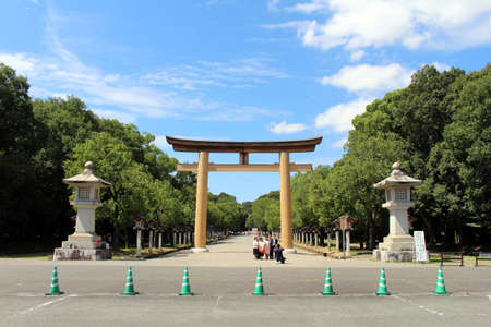 Japanese family taking photo in front of Entrance torii gate of Kashihara Jingu Temple. Taken in September 2019.