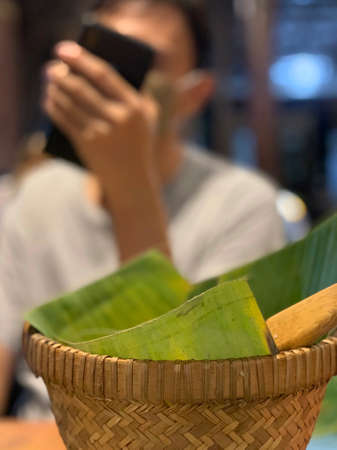 Basket of rice with leaves, and blurred background.