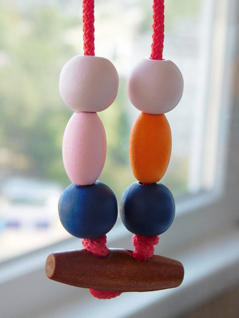 Colored wooden beads on red rope amulet.