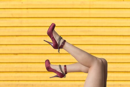 Perfect female legs with high heels isolated on yellow wooden background Banco de Imagens