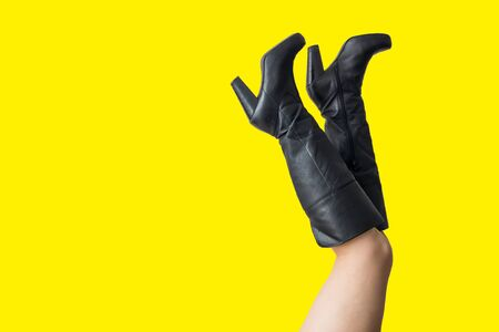 Perfect female legs with high heels isolated on yellow background