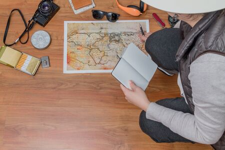 Lady planing a trip with a map and travel assets