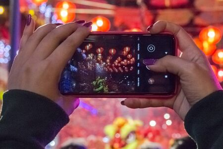 Woman's hands with cellphone recording the Chinese New Year festivities