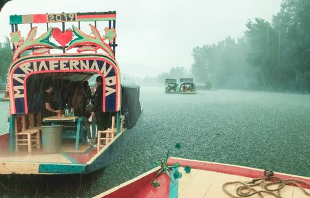 Xochimilco. CDMX. Mexico 25/08/2019 People enjoying a lake trip at trajineras, a traditional mexican boat in a rainy day.