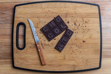 Chocolate bar with knife on wooden cutting board