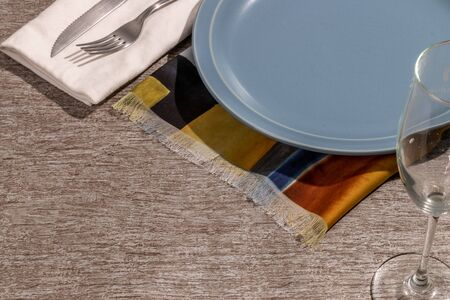 plate, cutlery wine glass and colored napkin on gray toned surface