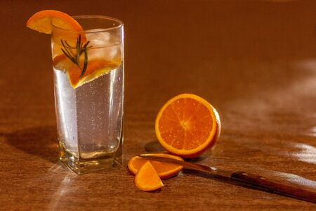 Natural orange drink with rosemary in warm tones