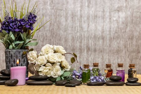 Composition of spa treatment, candles in bowl with water. Bottles of essential oil with dried rose petals, chamomile, calendula and incense resin on a Bamboo mat