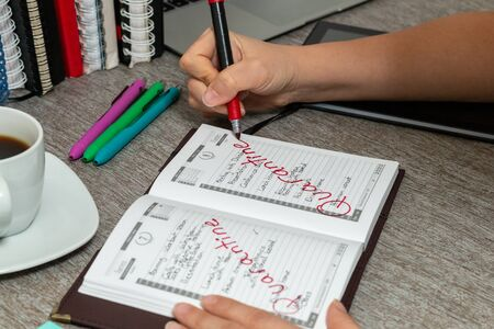 Scene of woman writes in a personal organizer about her coronavirus quarantine calendar.She is sitting at a desk. A laptop, a cup of coffee, notebooks and a notebook are on the desk.