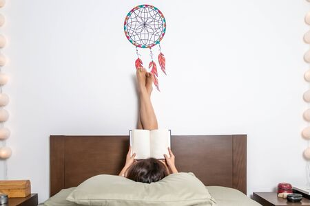 Happy brunette woman reading a magazine in bed, legs crossed
