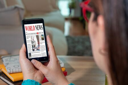 Online news on a mobile phone. Close up of the page of a businesswoman reading news or articles on a smartphone screen application. Smartphone with hand. Mockup website. Newspaper and Internet portal.