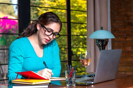 Real woman working from home. Hipster girl working in home office. make notes in a notebook