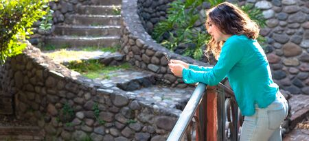 Woman using smartphone in the field. Real girl surfing the Internet with phone, texting and communicating outdoors. Travel concept 版權商用圖片
