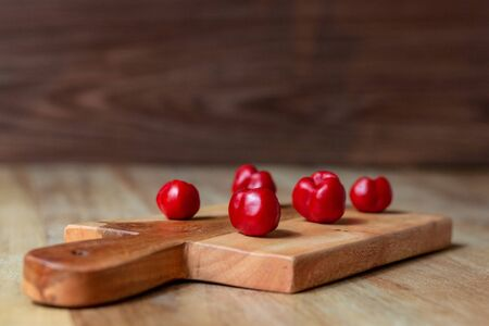 Apple and serrano peppers on chopping board on wooden surface. copy space