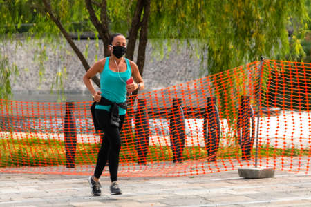 La Mexicana, Santa Fe, Mexico City: June 9, 2020. Athletic woman running during the quarantine for covid 19. New normality. surgical mask