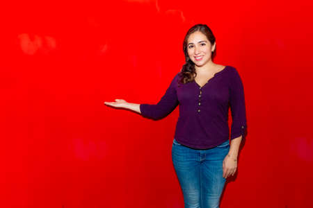 Image of a 30 year old caucasian woman with long brown hair looking at the camera and pointing with her fingers in the copy space isolated on red background