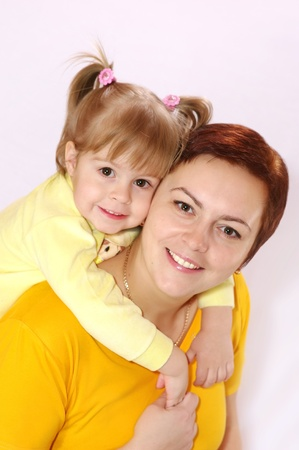 Portrait of mother and daughter. Small two-year baby hugs his mom Stock Photo