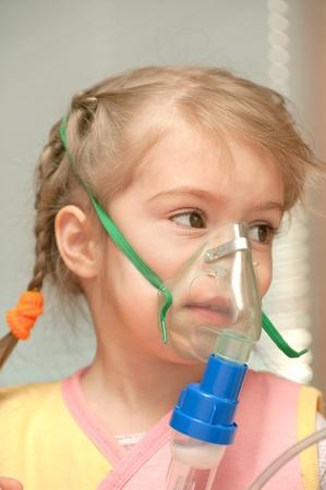 inhaler: A little girl three years doing inhalation