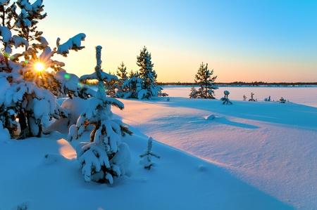 Beautiful sunset. Beach frozen lake.
