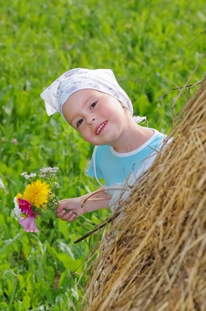 Baby playing hide and seek. The little girl looks out of the haystack.  Peekaboo. Stock Photo - 9059019