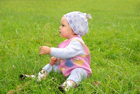 Baby on the street. A small child sits in the green grass on the lawn photo