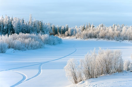 Traces of the snowmobile on the frozen river. Stock Photo - 9059046