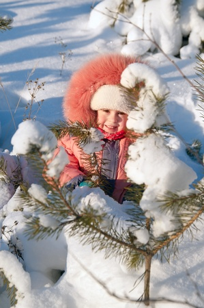 Child playing in snow. Little girl playing in the snow. The child hides behind a snow-covered tree Stock Photo