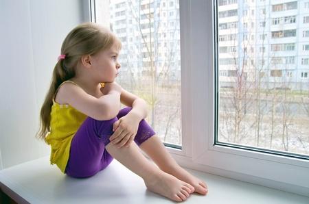 verdrietig meisje: Sad kind bij het raam. Een meisje van drie jaar in afwachting van de lente.