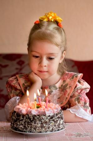 blow out: ?irthday. La bambina esprimere un desiderio prima di spegnere le candeline Archivio Fotografico
