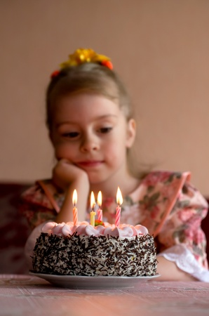 blow out: Birthday. The little girl make a wish before you blow out the candles Stock Photo