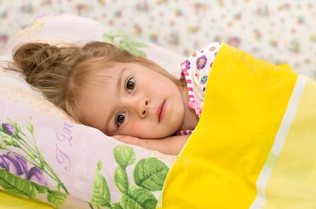 The little girl in bed. A little girl lying in bed with sad eyes Stock Photo