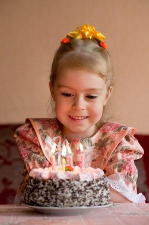 Ð'irthday. The little girl make a wish before you blow out the candles photo