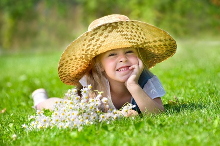 The little girl in the hat lying on green grass and laughing Stock Photo