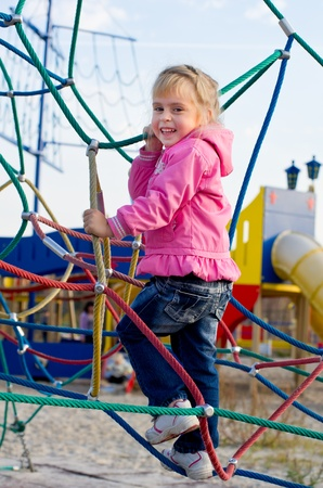 Cheerful little girl on the playground.  photo
