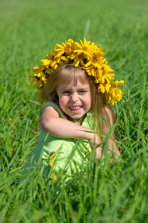 Cheerful little girl in a wreath of wild flowers photo